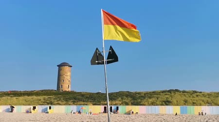 turistik : the beach of domburg with a red and yellow waving flag, touristic coastal city in zeeland, the Netherlands