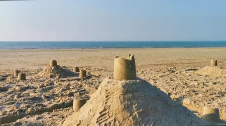Sand castles on the beach with the ocean in the background, summer holiday background video