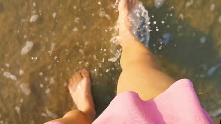 Female in a pink skirt walking with bare feet in the water, waves coming by, relaxation in nature Dostupné videozáznamy