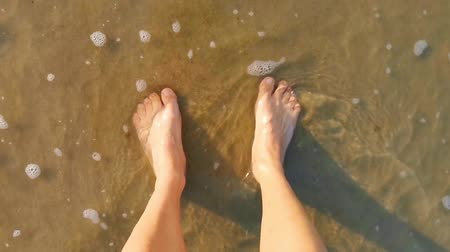 person standing with feet in the sand and water, sea waves coming by, relaxing in nature Dostupné videozáznamy