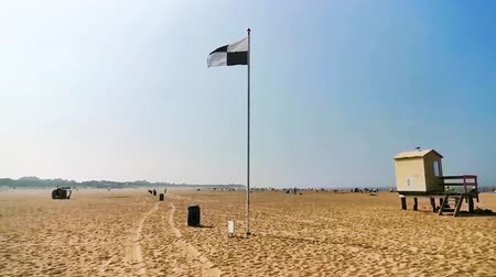 The beach of womens polder with a black and white checkered flag waving in the wind, water sports allowed sign, touristic coastal village in zeeland, the netherlands