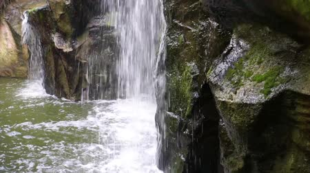 waterfall ending in the water, mossy rocks in closeup with flowing water, nature background