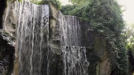 libra : multiple waterfalls streaming or a big rock cliff in a forest, mountain nature background