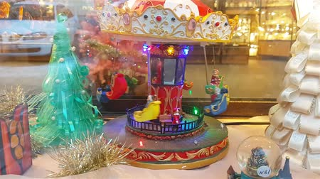 прикован : Tallinn, Estonia - January 8, 2018: Toy carousel in the window of a souvenir shop. Chained carousel with baskets in which the children are spinning on the background of a winter landscape. Street Viru