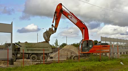 hydraulic : St.Petersburg, Russia - September 1, 2017: Excavator bucket loads heavy truck with ground on construction of highspeed road around Krasnoe Selo. Heavy industry machinery equipment for excavation works