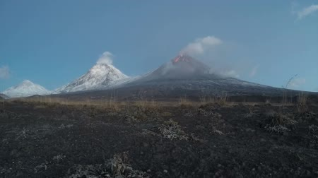 выброс : Volcanic landscape of Kamchatka (time lapse): morning view of eruption Klyuchevskoy Volcano, lava flows on slope of volcano; plume of gas, steam, ash from crater. Kamchatka Peninsula, Russian Far East, Klyuchevskaya Group of Volcanoes. Стоковые видеозаписи
