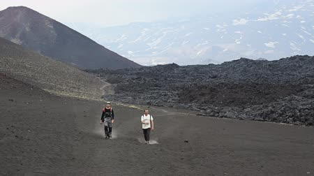 volcanology : TOLBACHIK VOLCANO, KAMCHATKA PENINSULA, RUSSIA - JUNE 24, 2016: Hiking on Kamchatka - two men tourists and travelers walk down the volcano after climbing to top active Tolbachik Volcano on Klyuchevskaya Group of Volcanoes.