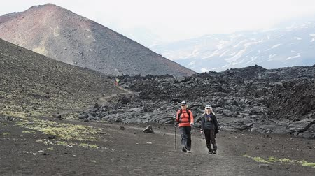 volcanology : TOLBACHIK VOLCANO, KAMCHATKA PENINSULA, RUSSIA - JUNE 24, 2016: Hiking on Kamchatka - woman tourists and travelers walk on tourist trail of slag on background of lava flow and cone of volcano on Klyuchevskaya Group of Volcanoes.
