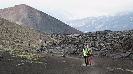 volcanology : TOLBACHIK VOLCANO, KAMCHATKA, RUSSIA - JUNE 24, 2016: Hiking on Kamchatka Peninsula - two young woman tourists and travelers walk down the volcano after climbing to top active Tolbachik Volcano on Klyuchevskaya Group of Volcanoes.