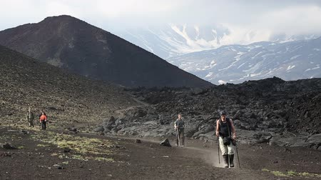 volcanology : TOLBACHIK VOLCANO, KAMCHATKA PENINSULA, RUSSIA - JUNE 24, 2016: Hiking on Kamchatka - group of tourists and travelers going on tourist trail of slag on background of cinder cone and lava flow on Klyuchevskaya Group of Volcanoes.
