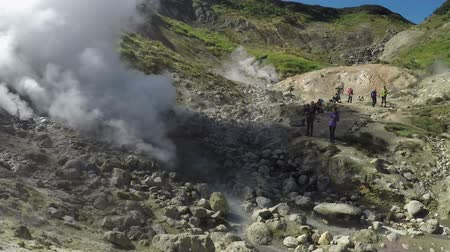 volcanology : DACHNYE HOT SPRINGS, KAMCHATKA PENINSULA, RUSSIA - SEP 15, 2016: Group of tourists on thermal field watching eruption natural volcanic Dachnye Hot Springs located at foot of active Mutnovsky Volcano.