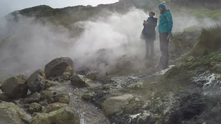 volcanology : DACHNYE HOT SPRINGS, KAMCHATKA PENINSULA, RUSSIA - SEPTEMBER 17, 2016: Young women tourists on thermal field watching at natural volcanic hot springs eruption large clouds of hot steam and gases.