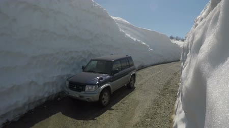 snowfield : KAMCHATKA PENINSULA, RUSSIAN FAR EAST - JUNE 18, 2017: Japanese off-road car Mitsubishi Pajero iO driving on highlands road in a snow tunnel on Vilyuchinsky Pass. Stock Footage