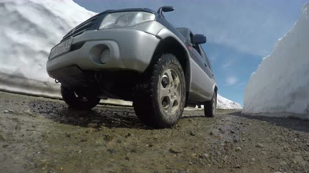 snowfield : KAMCHATKA PENINSULA, RUSSIAN FAR EAST - JUNE 18, 2017: Japanese off-road car Mitsubishi Pajero iO driving on a mountain road in a snow tunnel on Vilyuchinsky Pass.