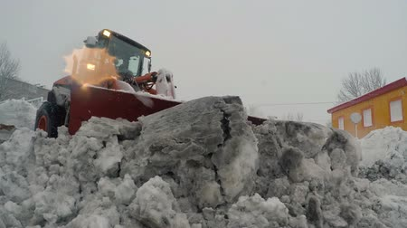 scrape : PETROPAVLOVSK KAMCHATSKY CITY, KAMCHATKA PENINSULA, RUSSIA - DEC 29, 2017: Front End Wheel Loader Hitachi clearing snow and ice from driveways during snowfall. Winter road maintenance in Petropavlovsk City
