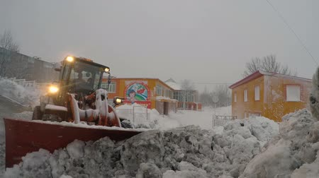 scrape : PETROPAVLOVSK CITY, KAMCHATKA PENINSULA, RUSSIA - DEC 29, 2017: Front End Wheel Loader Hitachi clearing snow from driveways to kindergarten during snowfall. Winter road maintenance in Kamchatka