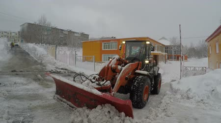 vég : PETROPAVLOVSK CITY, KAMCHATKA PENINSULA, RUSSIA - DEC 29, 2017: Front End Wheel Loader Hitachi clear snow from access road to kindergarten during snowfall. Winter road maintenance in Kamchatka