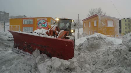 snow plow : PETROPAVLOVSK KAMCHATSKY CITY, KAMCHATKA PENINSULA, RUSSIA - DEC 29, 2017: Winter road maintenance - Front End Wheel Loader Hitachi removes snow from road to kindergarten during snowfall. Stock Footage