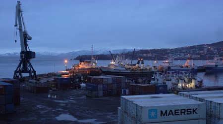 industrial fishing : KAMCHATKA PENINSULA, RUSSIAN FAR EAST - 27 APRIL, 2018: Night view of containers and fishing vessels trawlers at the pier Terminal Petropavlovsk City on the coastline of the Pacific Ocean