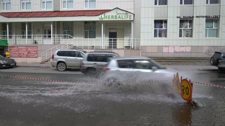szerkesztőségi : PETROPAVLOVSK KAMCHATSKY CITY, KAMCHATKA PENINSULA, RUSSIAN FAR EAST - 12 MAY, 2018: Cars driving on the central city of Puddle and splashing water from the wheels after heavy rain. Stock mozgókép