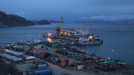 night scape : AVACHA BAY, KAMCHATKA PENINSULA, RUSSIA - 16 MAY, 2018: Evening view of crab processing ship, large freezing fishing trawlers and other fishing vessels docked in Petropavlovsk-Kamchatsky Sea Port.