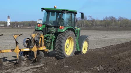 trator : KAMCHATKA PENINSULA, RUSSIA - 29 MAY, 2018: Tractor John Deere plowing rough land for initial cultivation of soil in preparation for sowing seed or turn soil stable. Agricultural work on sunny day.