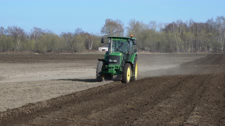 furrow : KAMCHATKA PENINSULA, RUSSIA - 29 MAY, 2018: Tractor John Deere plowing rough land for initial cultivation of the soil in preparation for sowing seed or planting to loosen or turn soil stable. Time lapse.