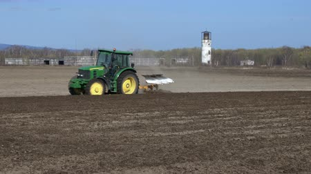 furrow : KAMCHATKA PENINSULA, RUSSIA - 29 MAY, 2018: Yellow-green modern tractor John Deere PowerTech plowing rough land for initial cultivation of soil in preparation for sowing seed or turn soil stable.