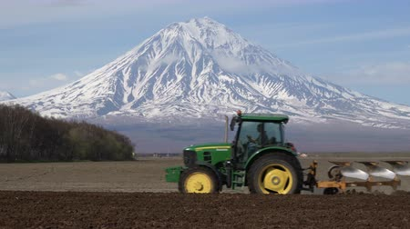 furrow : KAMCHATKA PENINSULA, RUSSIA - 29 MAY, 2018: Modern tractor John Deere ploughing rough land for initial cultivation of soil in preparation for sowing seed on background of active Koryaksky Volcano Stock Footage