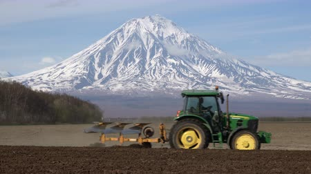 furrow : KAMCHATKA PENINSULA, RUSSIAN FAR EAST - 29 MAY, 2018: Modern tractor John Deere plowing rough land for initial cultivation of soil in preparation for sowing seed on background of active Koryak Volcano