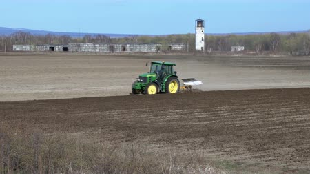 plough land : KAMCHATKA PENINSULA, RUSSIA - 29 MAY, 2018: Modern tractor John Deere ploughing rough land for initial cultivation of soil in preparation for sowing seed or turn soil stable. Farm work on sunny day. Stock Footage