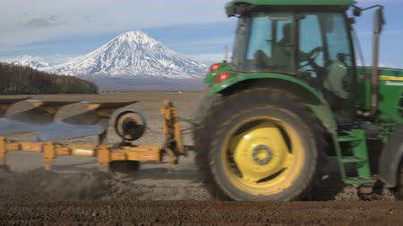 furrow : KAMCHATKA PENINSULA, RUSSIA - 29 MAY, 2018: Modern tractor John Deere PowerTech plowing rough land for initial cultivation of soil for sowing seed or planting to loosen or turn stable
