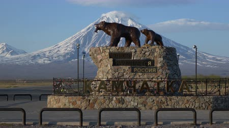 petropavlovsk : KAMCHATKA PENINSULA, RUSSIA - MAY 30, 2018: Sculpture of Kamchatka brown bear family, she-bear with bear cub, inscription: Here begins Russia. Kamchatka. Monument on background of volcano. Time lapse