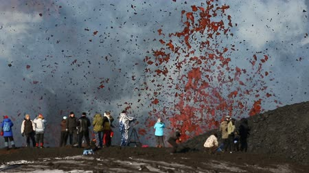 volcanology : TOLBACHIK VOLCANO, KLYUCHEVSKAYA GROUP OF VOLCANOES, KAMCHATKA PENINSULA, RUSSIA - FEB 2, 2013: Group of tourists photograph of the fountain of flying red hot lava, eruption from crater of active volcano.