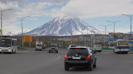 příjezdová cesta : PETROPAVLOVSK CITY, KAMCHATKA PENINSULA, RUSSIA - 2 JUNE, 2018: Automobiles driving along asphalt city road on the background of majestic cone of active Koryakskaya Sopka or Koryak Volcano. Time lapse Dostupné videozáznamy