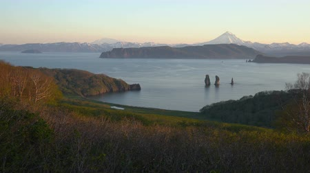 eurasia : Pacific Coast of Kamchatka Peninsula: stunning summer seascape, rocky mountains and volcanoes on shores of Avacha Bay on sunny weather. Popular travel destinations in Russian Far East. Time lapse