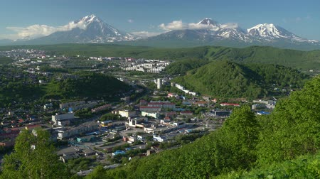 daleko : PETROPAVLOVSK CITY, KAMCHATKA PENINSULA, RUSSIAN FAR EAST - JULY 8, 2018: Summer view of the cityscape of Petropavlovsk-Kamchatsky on the background of majestic volcanoes surrounded by mountains. Time lapse
