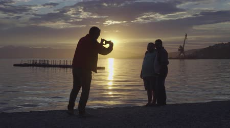 port n : AVACHA BAY, KAMCHATKA PENINSULA, RUSSIA - 10 JULY, 2018: Friends - tourists and visitors standing on a pebble beach in seaport and take pictures on a background of colorful sunset over Pacific Ocean. Stock Footage