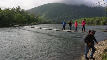 daleko : FAST RIVER, KAMCHATKA PENINSULA, RUSSIAN FAR EAST - AUGUST 4, 2018: Group of travelers and tourists cross mountain river on a suspended bridge, dangerously low hanging low over stormy cold water. Dostupné videozáznamy