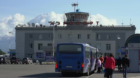 petropavlovsk : KAMCHATKA PENINSULA, RUSSIAN FAR EAST - AUG 6, 2018: Commercial airport terminal, passengers on station square boarding an intercity bus driving from airport to Petropavlovsk-Kamchatsky City. Stock Footage