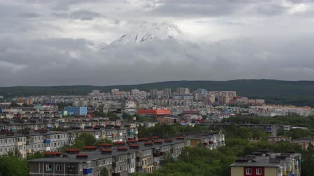 petropavlovsk : Summer cityscape of Kamchatka Peninsula: view of urban development of Petropavlovsk-Kamchatsky City on background of volcano, clouds floating across sky, around mountains. Russian Far East. Time lapse