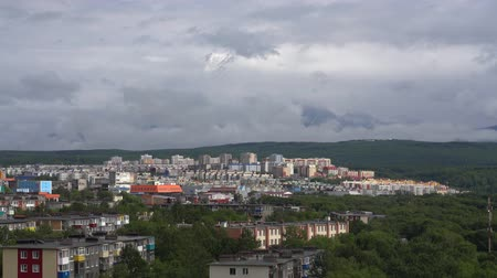 eurasia : Summer view of the townscape of Kamchatka Peninsula: urban development of Petropavlovsk-Kamchatsky City on the background of volcano, clouds floating across the sky, around mountains. Russian Far East. Time lapse