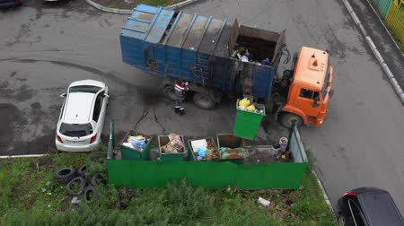 petropavlovsk : PETROPAVLOVSK CITY, KAMCHATKA PENINSULA, RUSSIAN FAR EAST - AUG 16, 2018: Top view on driver of garbage truck KAMAZ loading municipal container with garbage into its bins with help of manipulator. Stock Footage