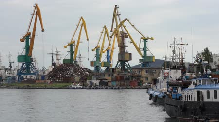skalní útes : PETROPAVLOVSK CITY, KAMCHATKA PENINSULA, RUSSIAN FAR EAST - 4 SEP, 2018: Port crane works with scrap metal; operate on pier in Pacific Commercial Seaport of Petropavlovsk-Kamchatsky City. Time lapse