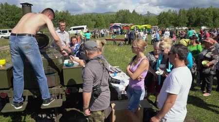 osvětlovací zařízení : KAMCHATKA PENINSULA, RUSSIAN FAR EAST - 25 AUGUST, 2018: Large group of people stand in line for free fish soup cooked in green mobile military food truck in summer sunny weather. Dostupné videozáznamy