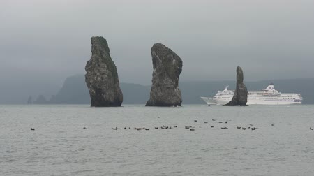 pacific islands : AVACHA BAY, KAMCHATKA PENINSULA, RUSSIA - 6 SEP, 2018: Stunning seascape - Japanese cruise liner Pacific Venus sailing near rocky islands in the sea - Three Brothers Rocks in Pacific Ocean on a cloudy day.