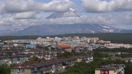 daleko : Summer townscape of Kamchatka Peninsula: view of urban development of Petropavlovsk-Kamchatsky City on background of volcano clouds floating across the sky, around rocky mountains on sunny day. Time lapse Dostupné videozáznamy