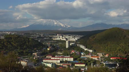 petropavlovsk : PETROPAVLOVSK KAMCHATSKY CITY, KAMCHATKA PENINSULA, RUSSIAN FAR EAST-SEP 22, 2018: Autumn panoramic cityscape: urban development on a background of volcanoes and clouds floating across the sky. Time lapse