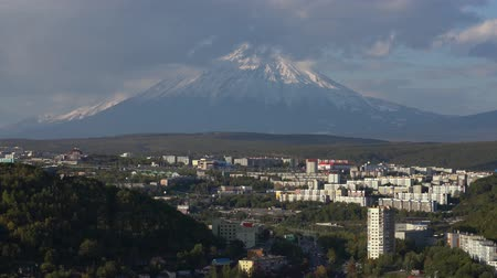daleko : PETROPAVLOVSK CITY, KAMCHATKA PENINSULA, RUSSIA - SEP 22, 2018: Autumn townscape urban development of Petropavlovsk-Kamchatsky City on background of active Koryaksky Volcano, clouds floating across sky Dostupné videozáznamy