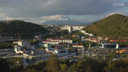 petropavlovsk : PETROPAVLOVSK CITY, KAMCHATKA PENINSULA, RUSSIA - SEP 22, 2018: Autumn panorama townscape urban development of Petropavlovsk-Kamchatsky City on background of Koryak Volcano, clouds floating across sky Stock Footage